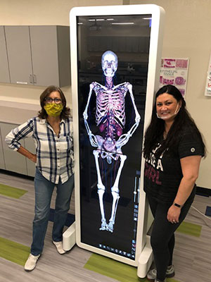 Vigil and student standing next to a large touchscreen with a human anatomical diagram displayed on it.