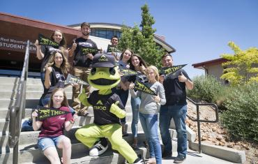 Mascot Wizard the Lizard with students on the steps of the Red Mountain Building