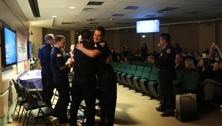 Cadets hugging at the fire academy graduation.