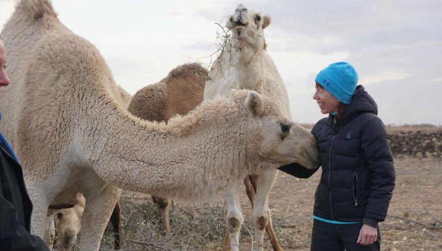 Namie standing next to two camels.