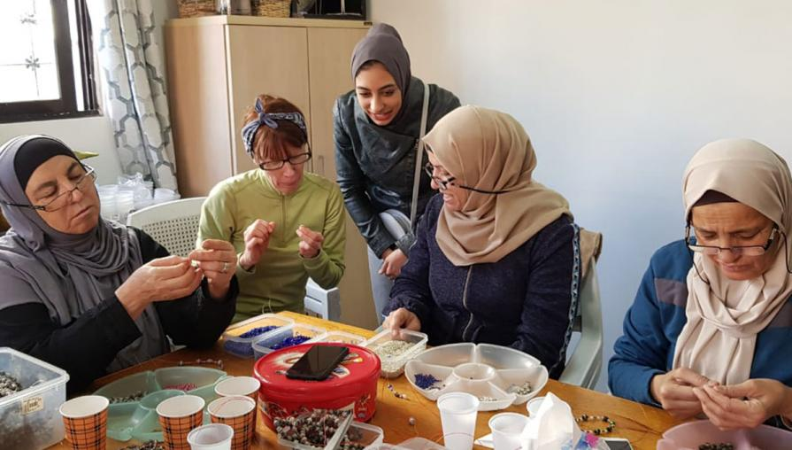 Women sitting around a table, making beaded jewelry.