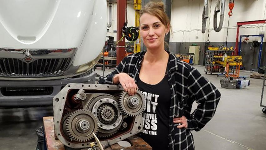 TMCC student Laurel Allen standing with an automobile engine.