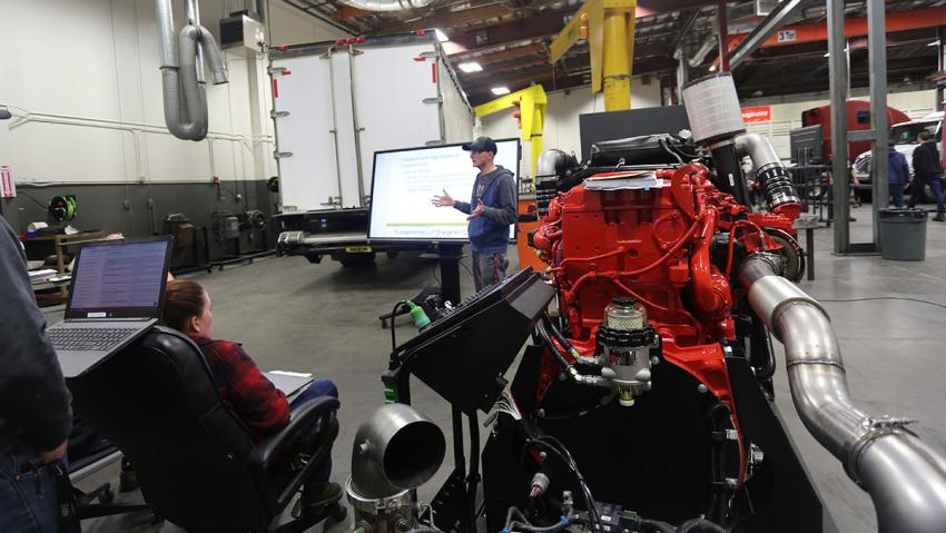 Students in an automotive lab using a large touch screen planel.