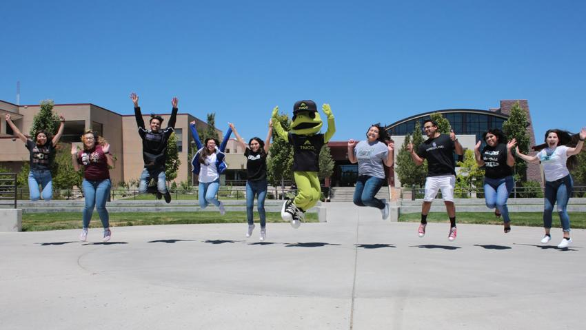 TMCC students and mascot jumping in the air.