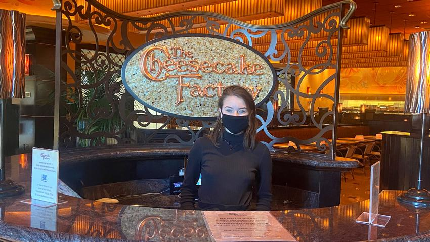 TMCC Hospitality and Tourism graduate Emily Lorge working as a hostess at The Cheesecake Factory