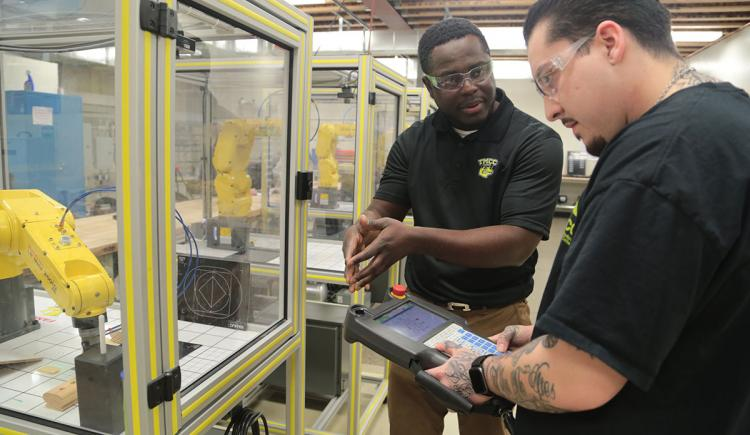 Instructor working with a student in a technology lab.