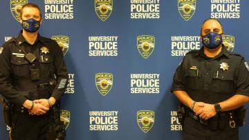 Two police officers standing in front of a University Police Services banner.