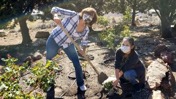 Cecilia Vigil digging outdoors with a student.