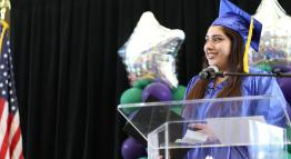 Photo of a student wearing graduation robes on a stage.