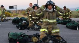 Fire cadets don their gear outdoors.