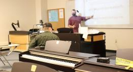 A masked instructor teaches students in a music classroom.