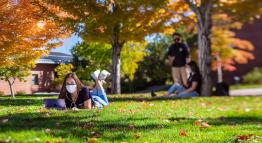 Students sitting outdoors on the grass.